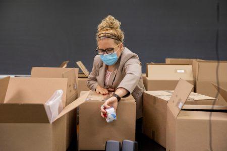 Visiting biology professor Erin Heller gets lab kits ready to ship.