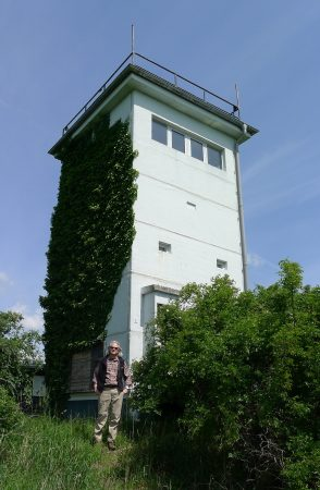 Randolph philosophy professor David Schwartz poses in front of a defunct East German watchtower used during the Cold War.