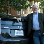 President Bradley W. Bateman leans on his eco-friendly Prius car with custom Randolph license plate