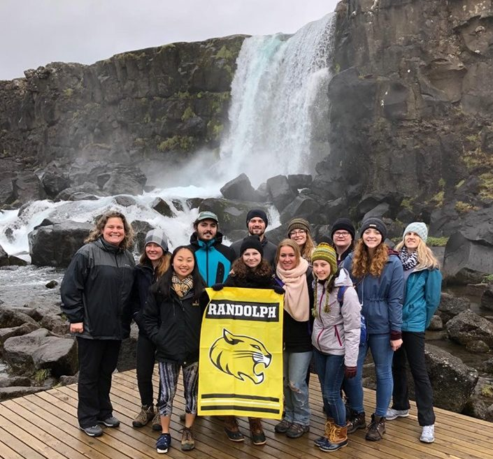 Students and faculty hold a Randolph banner in front of a waterfall in Iceland