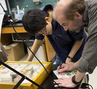Professor and student examine artifacts.