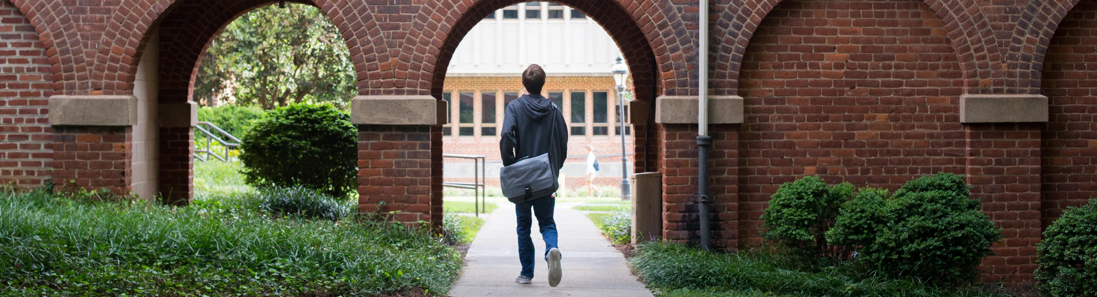 Photo of student walking through campus.