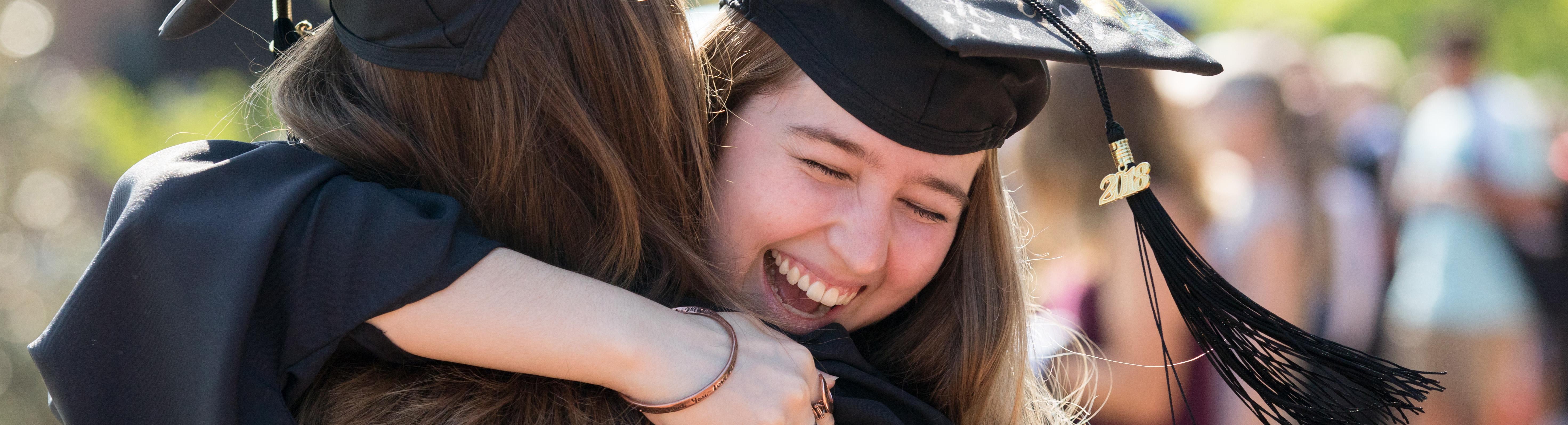 Students hugging at graduation.