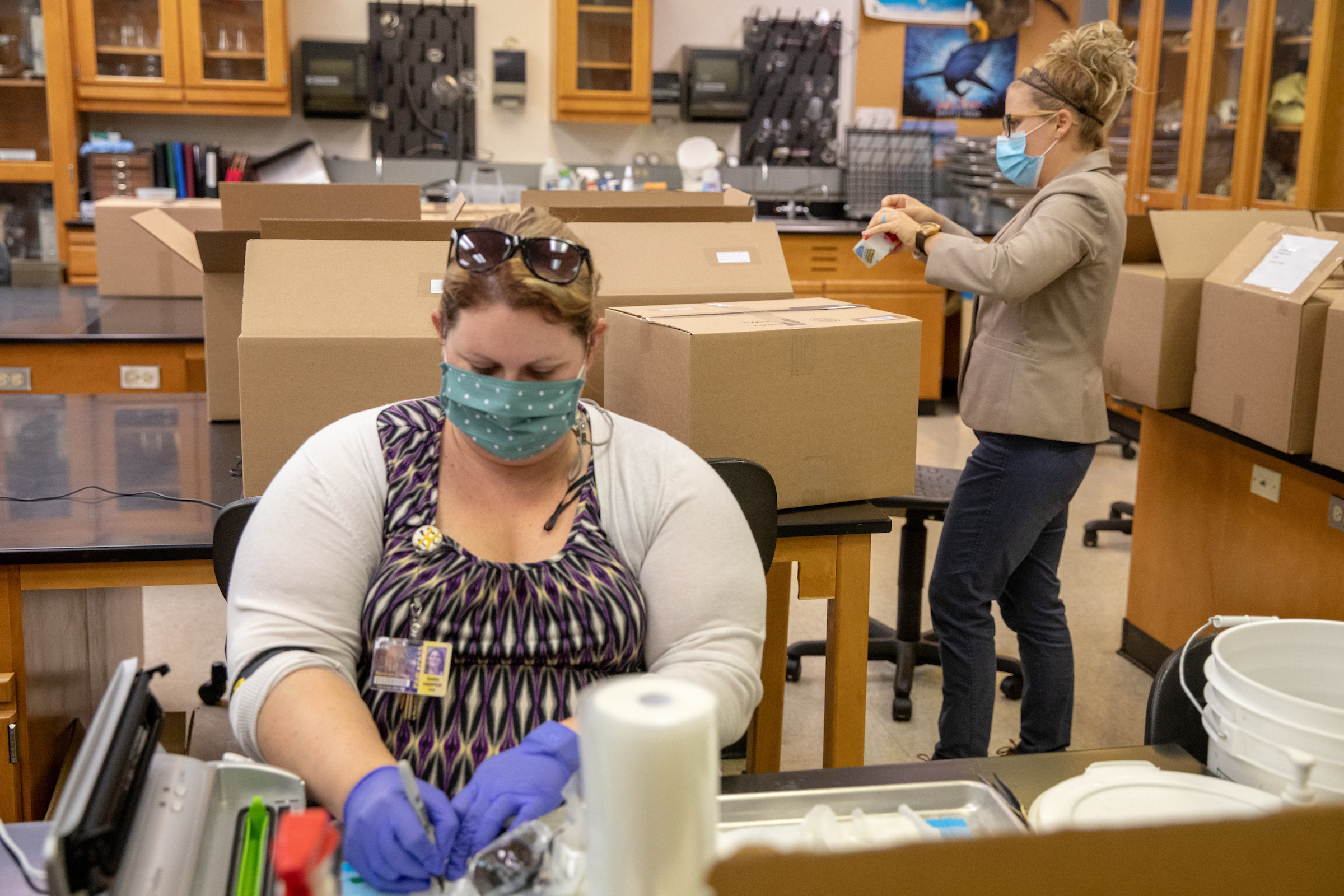 Biology lab technician Sara Harper and visiting biology professor Erin Heller put together lab kits for students taking Heller