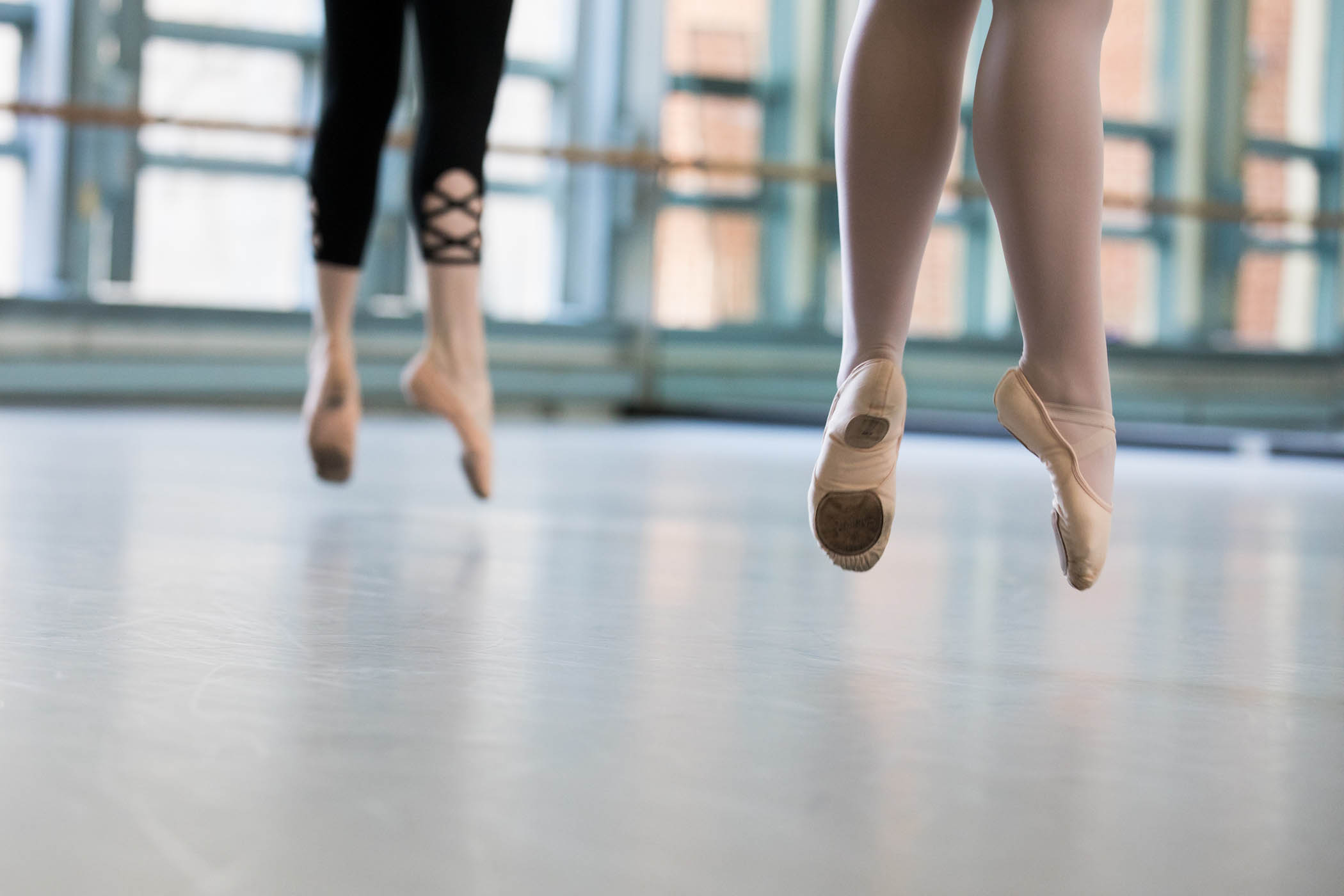 Feet of two dancers in the air