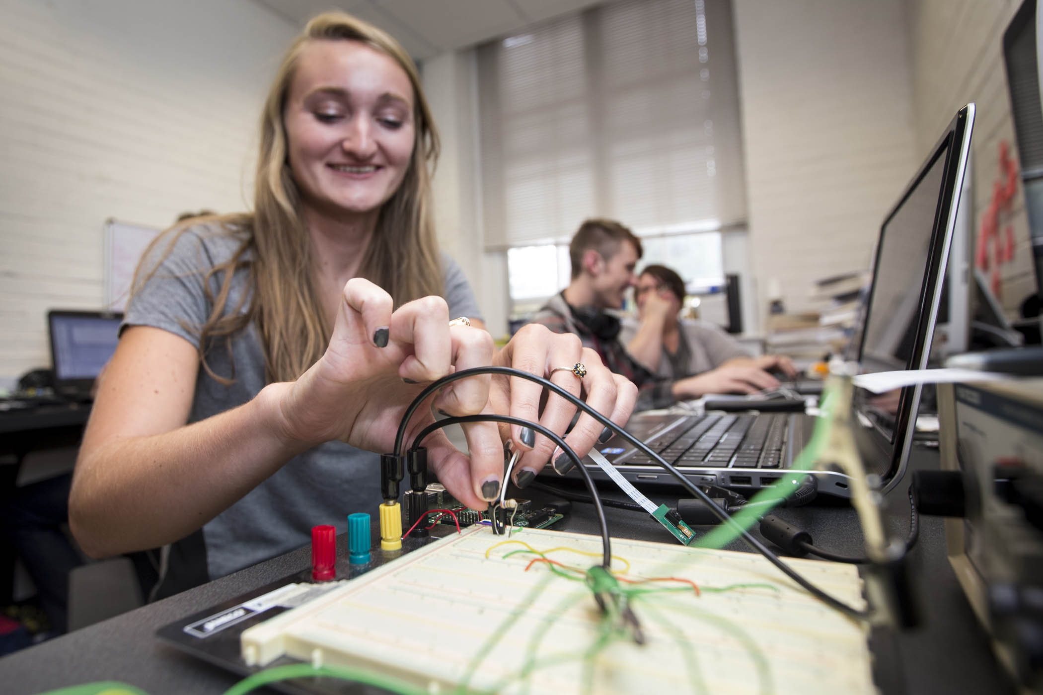 Student checks electrical connections on instruments