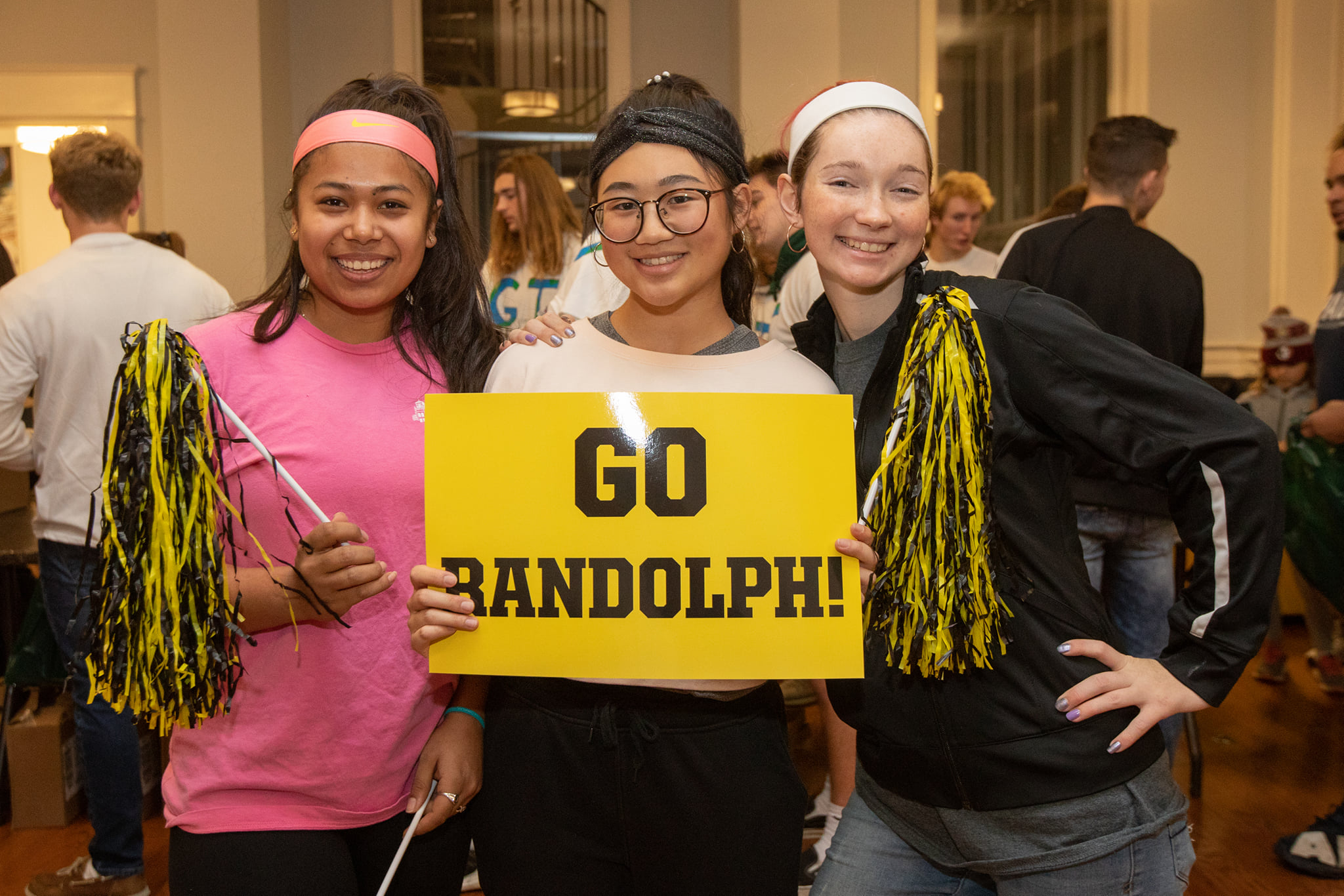 "Three students pose with a sign that reads ""Go Randolph"""