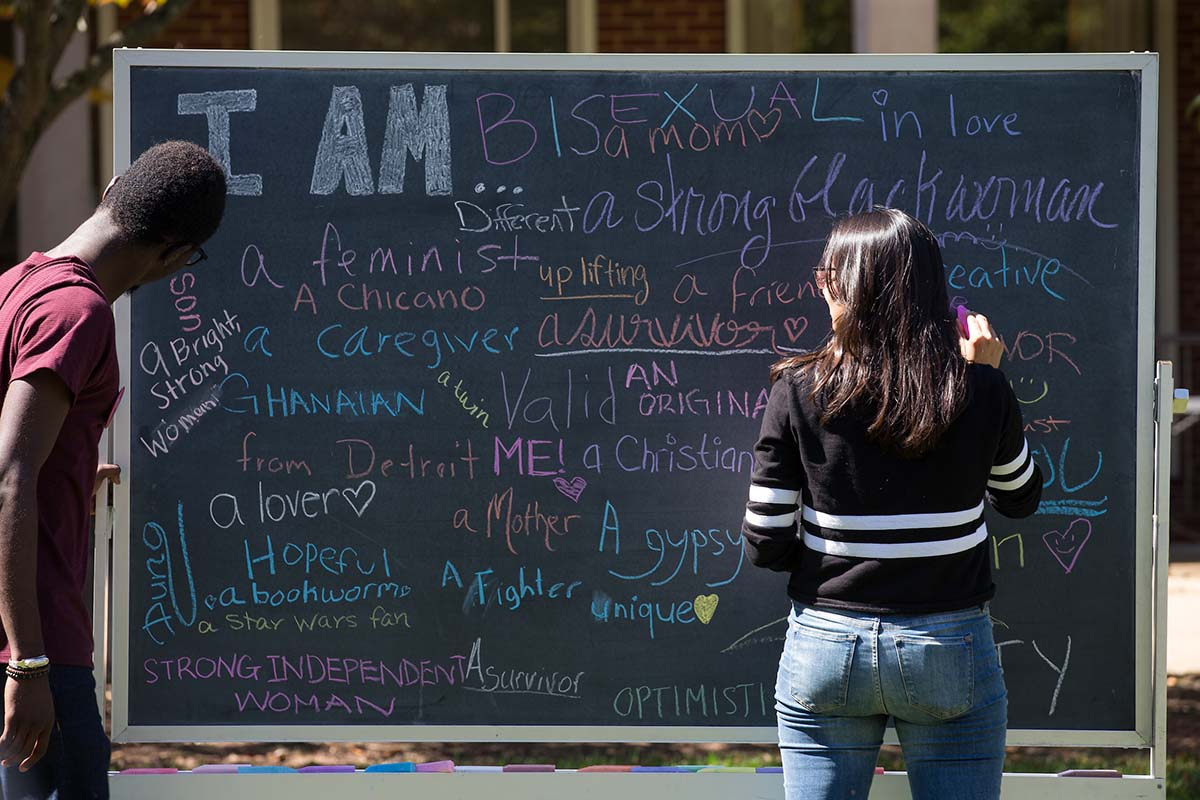 Students share their identities on a diversity chalkboard.