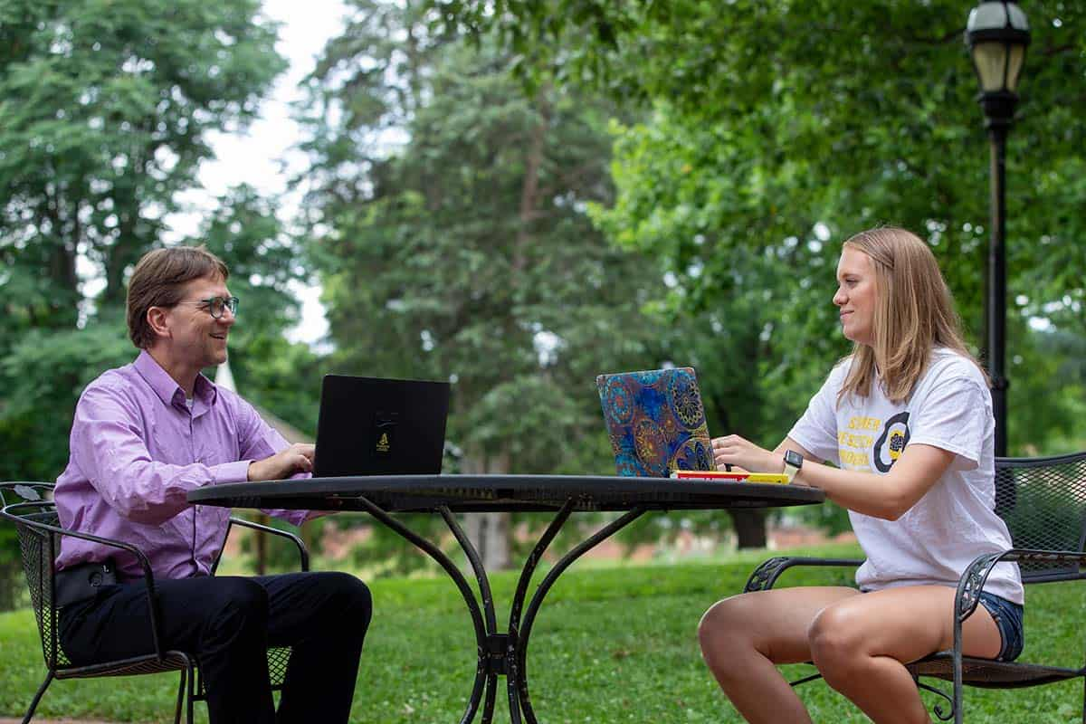 Professor Peter Sheldon meets with a student at an outdoor table.