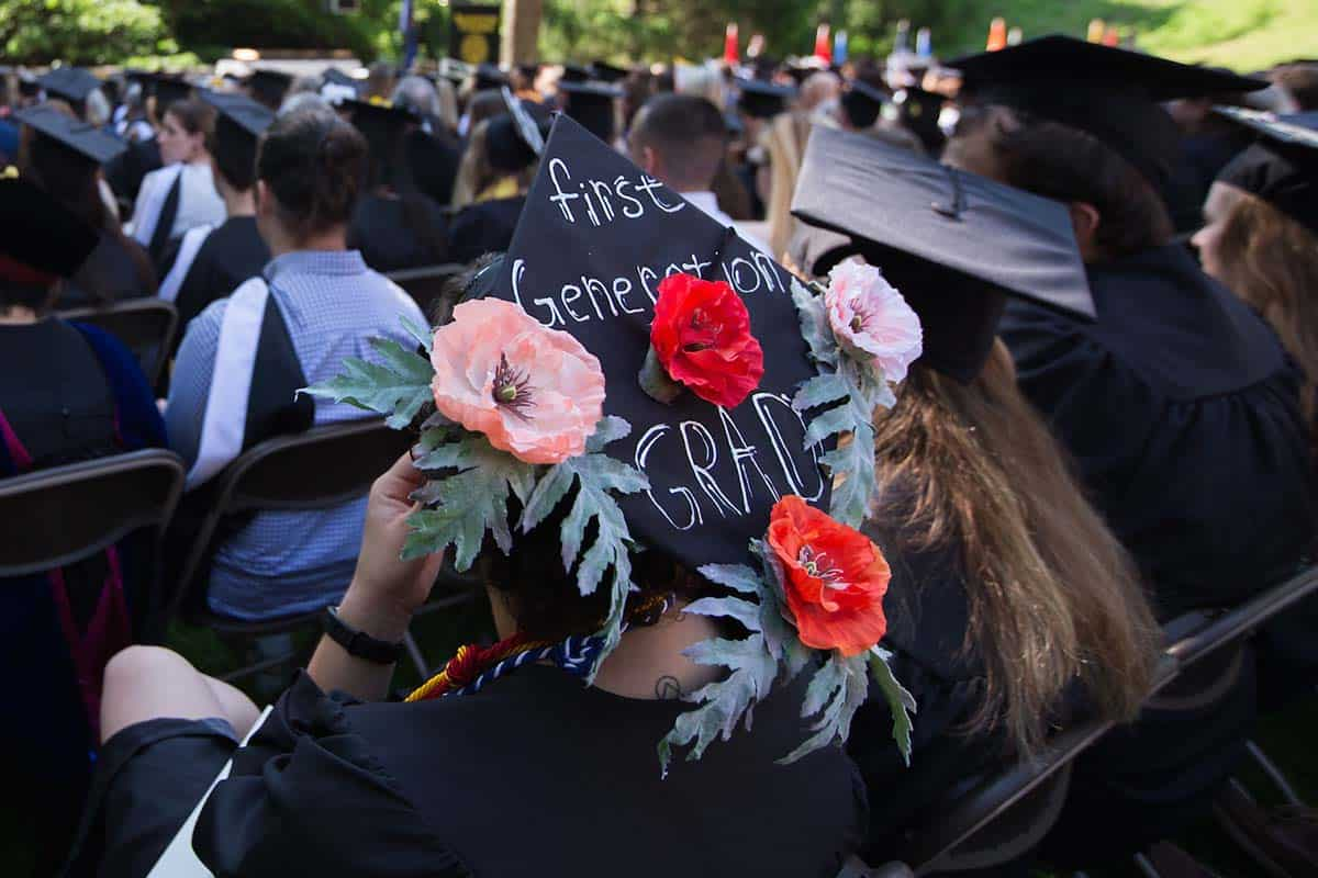 Graduating student wears a cap decorated with flowers and the words First Generation Grad.