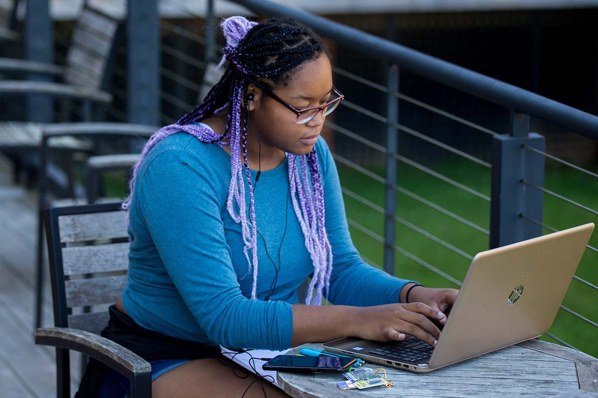 Female student works on her wi-fi connected laptop on the patio outside the Student Center.