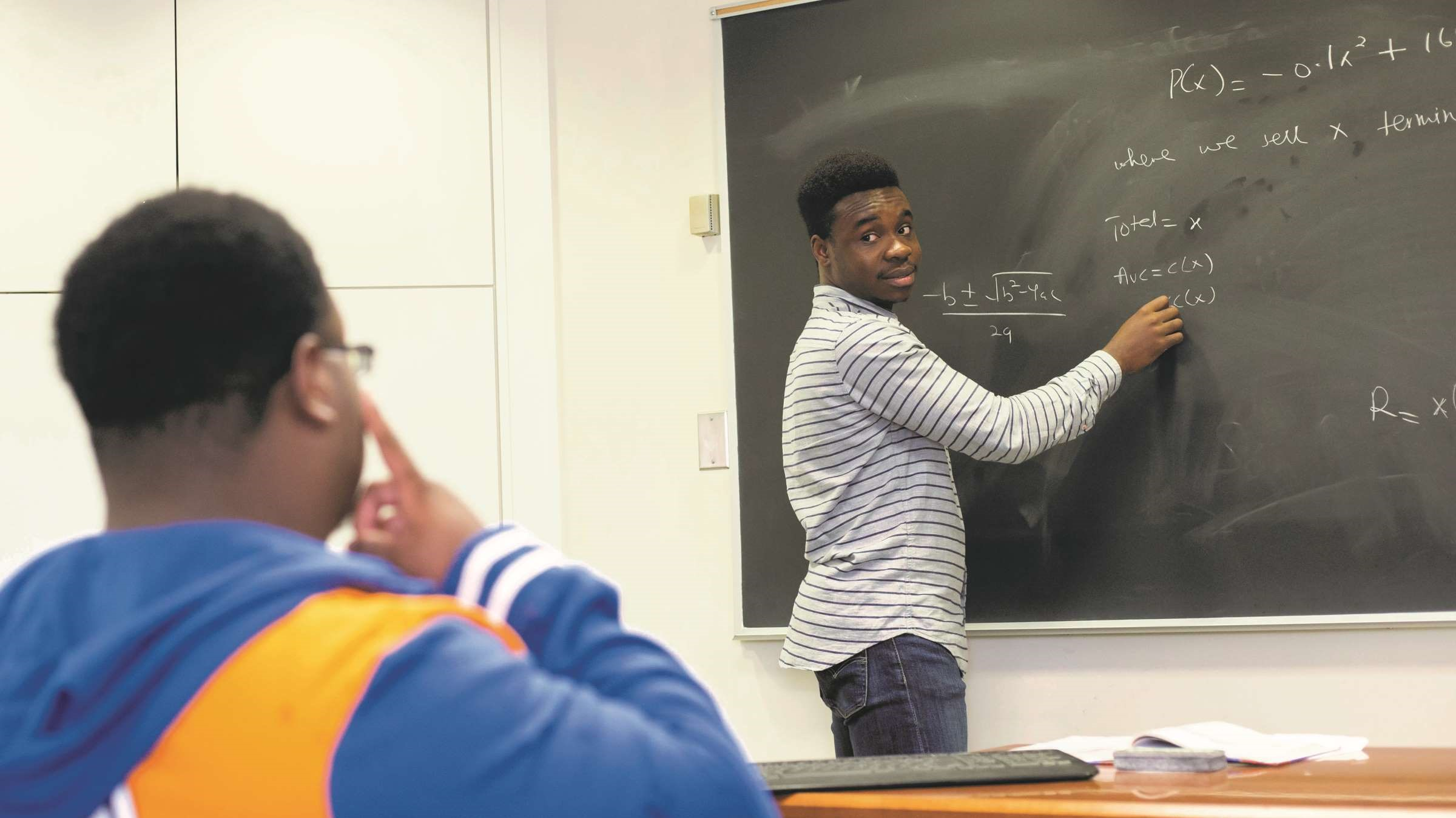 Student solves math problem on chalkboard in front of class.