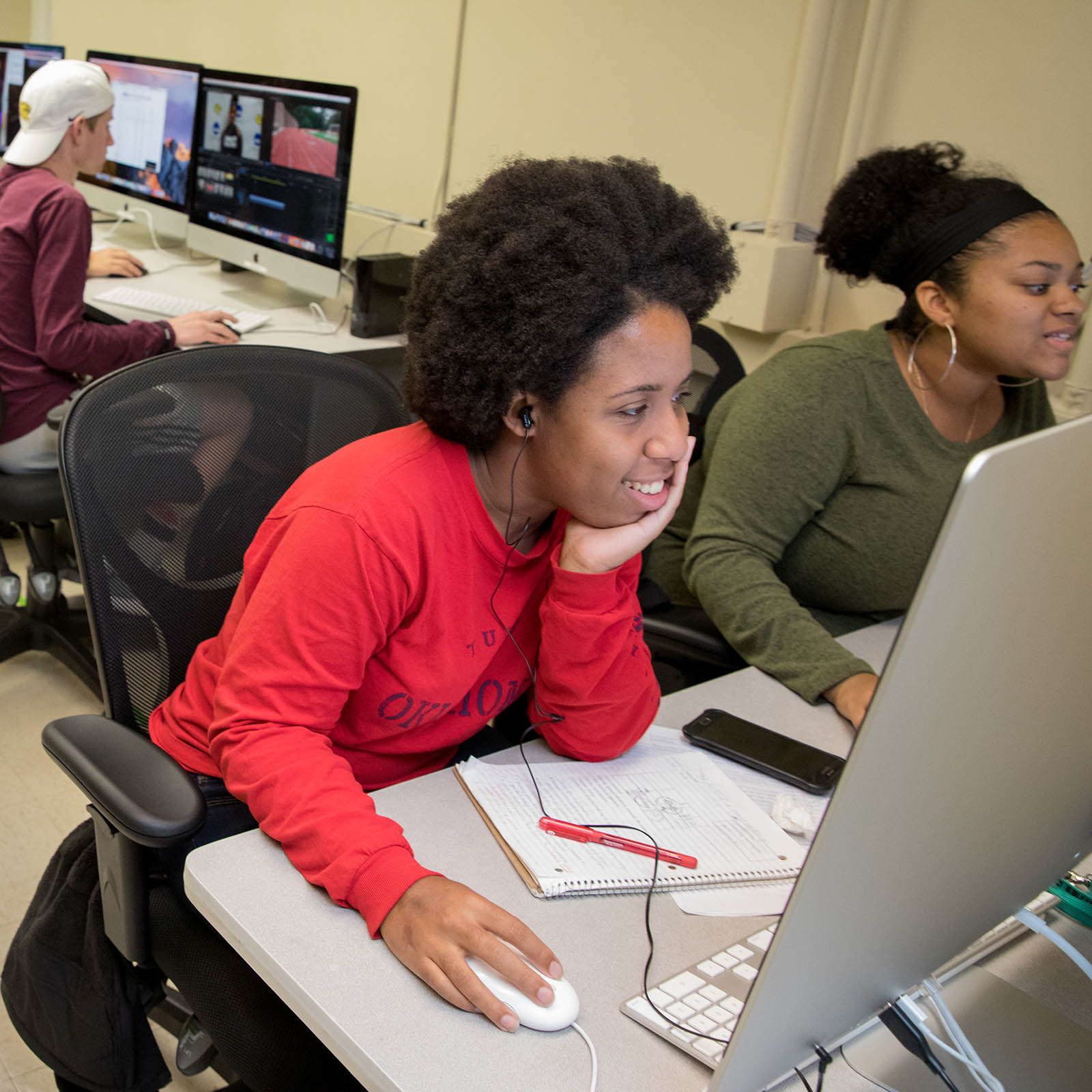 Female students edit video in the Randolph College media lab.