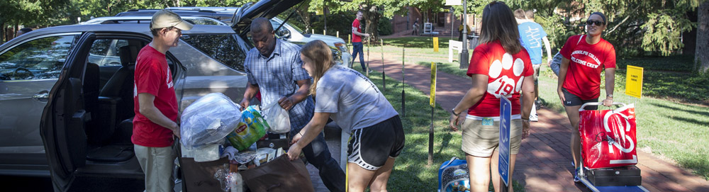 Students help new students and their families unload their cars