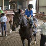 Camp volunteers help children saddle up.