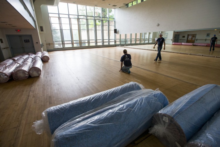Workers prepare to install the new padded vinyl floor in the dance studio at Randolph College.