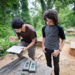 Hagay Haut (left) of Randolph College and E.C. Glass student Spencer Cohen take readings on temperature and humidity for the tiny houses they built on campus. (Photo by Jill Nance)