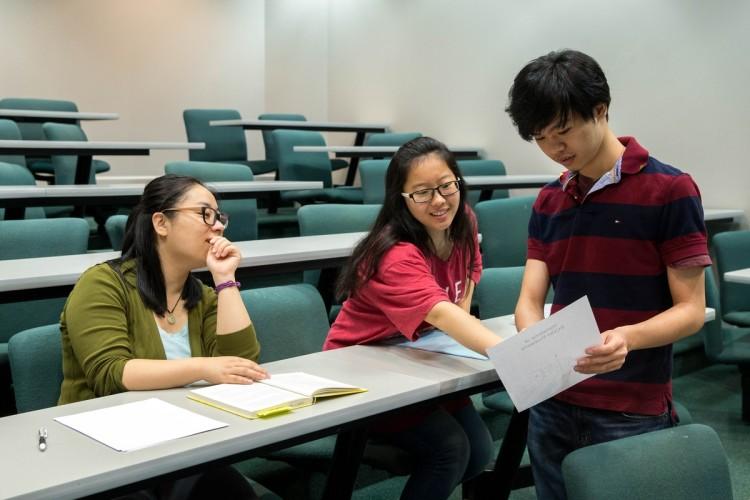 Mathematics professor Jia Wan observes as Mengjin Sun '19 and Nhut Dang '18 study an equation.