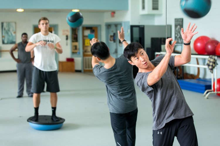 Visiting dance professor Seyong Kim works out with students in Men's Movement class.