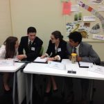 Members of the 2016 Ethics Bowl team discuss their answer to a question.