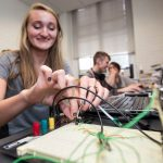 A physics student configures a device that tracks sound levels as part of a Summer Research project.