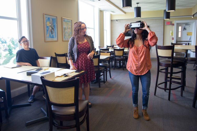 Dung Nguyen '18 (left) and psychology professor Blair Gross watch as Avisha Shah '18 uses the Oculus virtual reality headset.