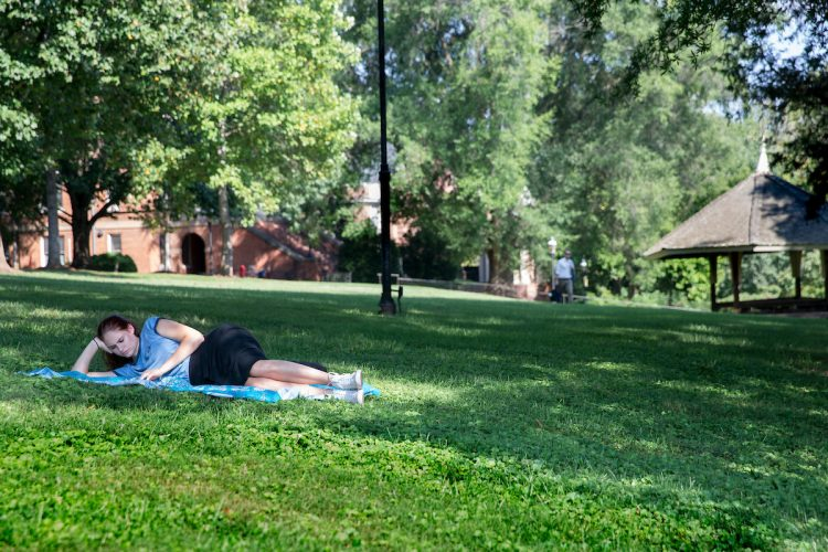 Student laying on the grass, studying on front campus