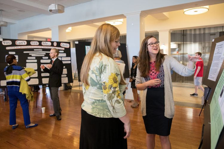 Students explain their work at the poster presentation in the Hampson Commons