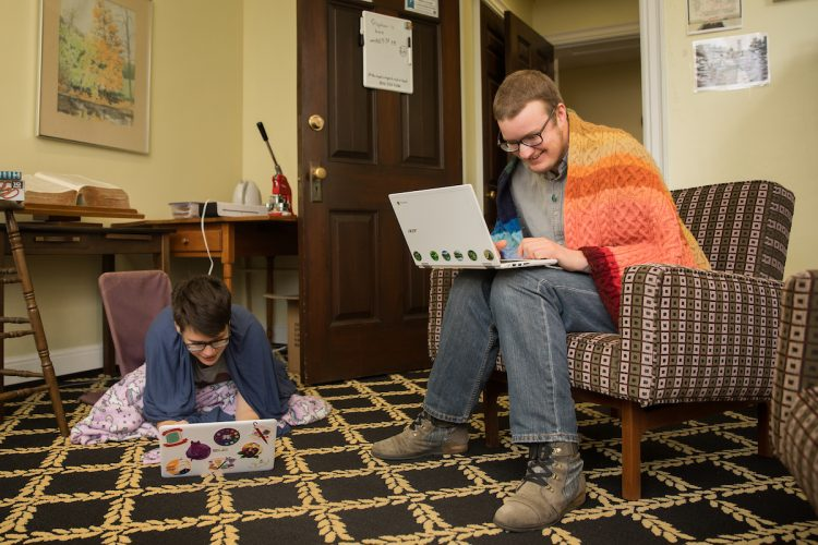 Lewis Ward '20 and Stephen Krueger, access and outreach services librarian at Randolph, work together in the Lipscomb Library.