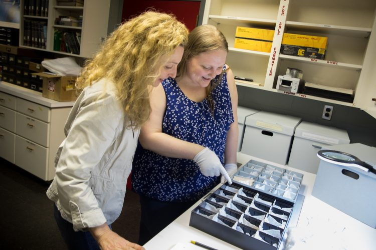 Art history professor Andrea Campbell and Sara Primm '20 look at glass samples from Randolph's archaeology collection