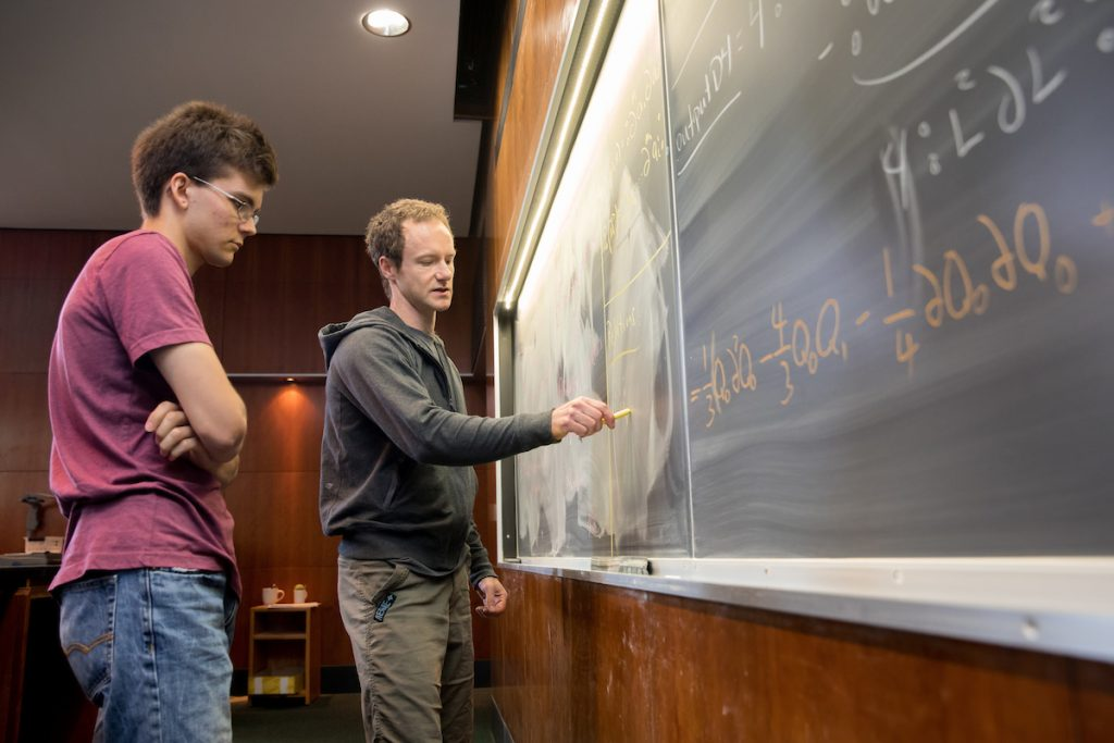 Jude Quintero '20 (left) and mathematics professor Michael Penn work on an equation