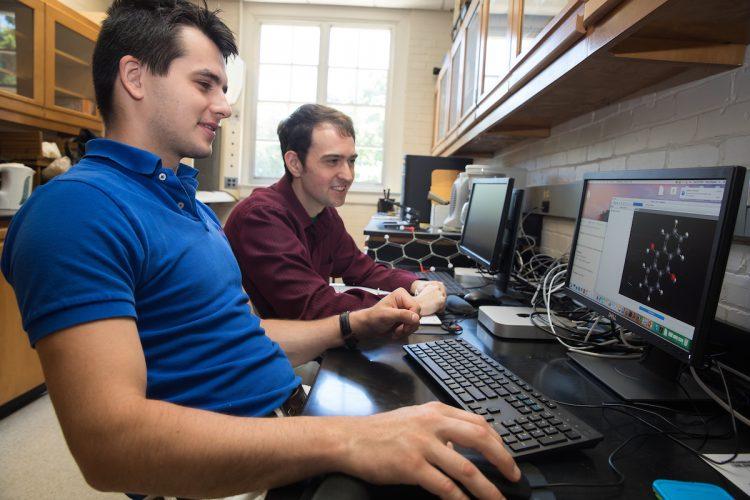 Yuriy Snyder '19 (left) and chemistry professor Jesse Kern test a molecule using computational modeling software