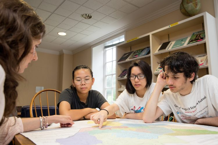 """Professor Liz Perry-Sizemore, San Hoang '20, Anh """"Jessica"""" Bui '20, and Leo Cohen look at a map of Lynchburg."""