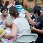 Students and alumnae have conversations over dinner at the College Community Cookout