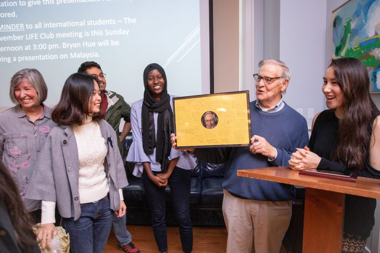Vic Uotinen receives a framed photo with international student signatures
