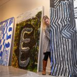 Elisabeth Ayars '19 sets up paintings for the spring exhibitions that will open this Friday.