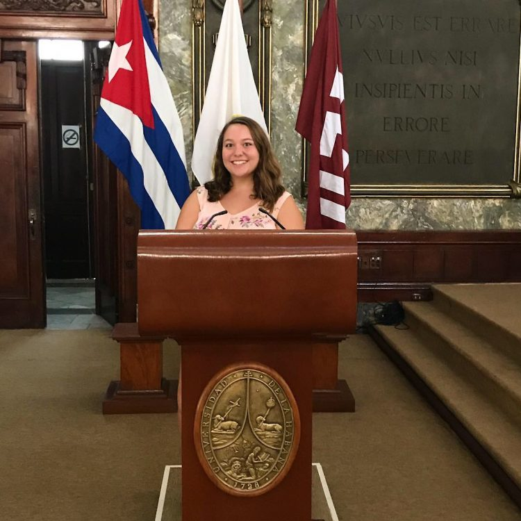 Lauren Appel '20 at the podium in a Cuban government building