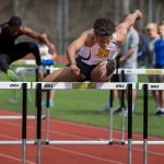 DJ Petty '20 jumps a hurdle at a Randolph track meet in 2018