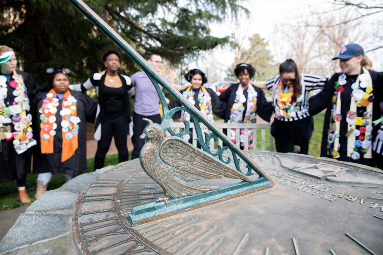 Students sing school songs around the Sundial