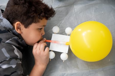 Students blow up balloons for a propelled car at Science Festival.