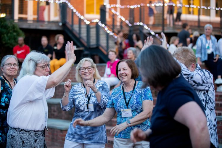 A group of alumnae dance in Michels Plaza
