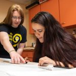 Professor Heather Sinclair (left) and Karyn Heisig draw stage renderings