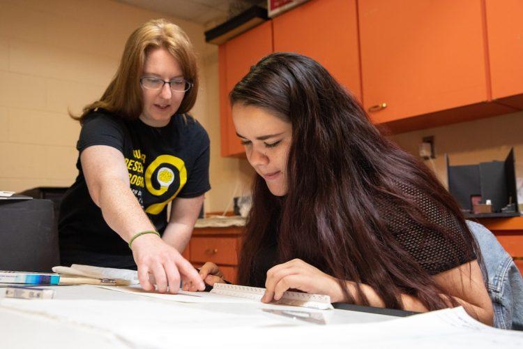 Professor Heather Sinclair (left) and Karyn Heisig draw stage renderings