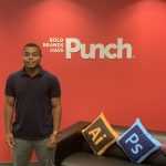 Jared Ruddock in front of red wall with Punch logo on it