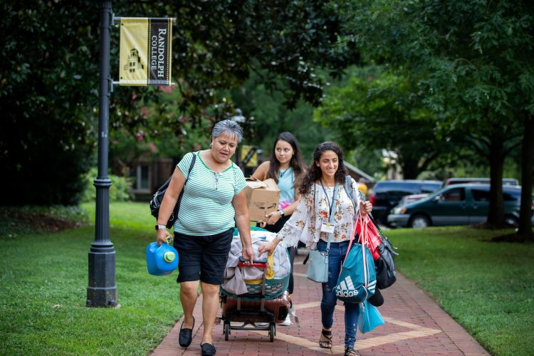 Student and family members wheel luggage along the brick path on front campus
