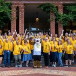 Faculty and staff volunteers pose with Wanda WildCat on the front steps of Main Hall
