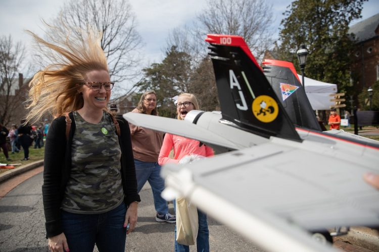 A visitor gets her hair blown back by a mini jet engine at the 2019 Science Festival.