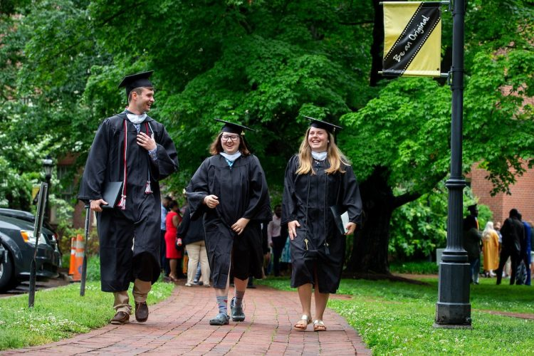 Graduates walk along the Red Brick Path on front campus