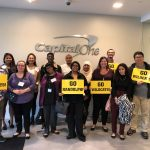 Students and Capital One staff pose with signs that read,
