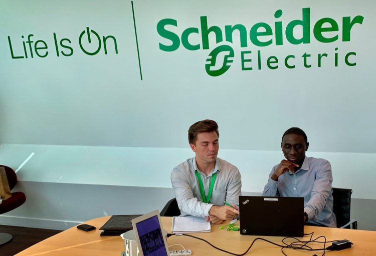 Anthony Fonnesu works with a colleague at Schneider Electric